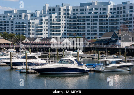 Yachts moored at Marina Bay docks, in front of a waterfront boardwalk, restaurants and condominium complex, in Quincy, Massachusetts, USA. - Stock Photo