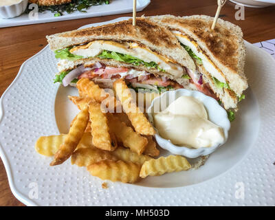 Chicken sandwich and French fries with mayonnaise sauce on white plate at restaurant. - Stock Photo