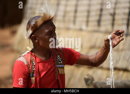 Eshowe, KwaZulu-Natal, South Africa, single young man in traditional Zulu dress explaining cultural customs of beadwork at Shakaland theme village - Stock Photo