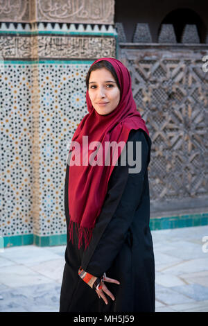 Muslim woman posing in traditional clothing with red hijab and black dress in front of traditional arabesque decorated wall - Stock Photo