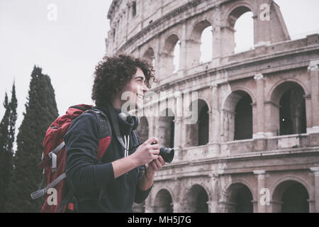 Handsome young tourist man with curly hair with a camera and backpack taking pictures of Colosseum in Rome, Italy. Vintage looking image of young tour - Stock Photo