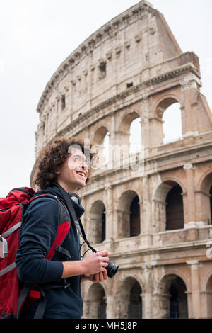 Handsome young tourist man with curly hair with a camera and backpack taking pictures of Colosseum in Rome, Italy. Young tourist taking pictures of Co - Stock Photo
