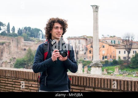 Handsome young tourist with curly hair taking photos of Roman forum in Rome, Italy. Young man travel with his camera - Stock Photo