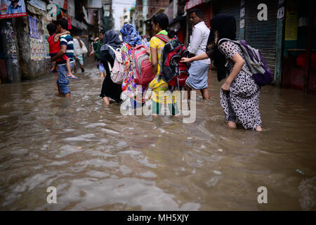 Dhaka, Bangladesh. April 30, 2018. Dhaka city dwellers ride rickshaw through the flooded road after the heavy rainfall in Dhaka, Bangladesh on April 30, 2018. Al least 14 people have killed during the lightning and thunderstorms, disrupting life in the capital city where heavy rain flooded many roads according to reports.  Credit: Rakib Hasan/Alamy Live News - Stock Photo