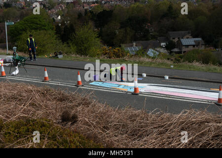 Ilkley Moor, West Yorkshire, UK. 30th April 2018. Artists, spending hours on their knees, paint the Tour de Yorkshire's first summit finish on the Cow and Calf road ready for Friday's race.  What's it going to be? (anamorphic land art) Rebecca Cole/Alamy Live News - Stock Photo