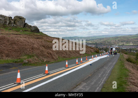 Ilkley Moor, West Yorkshire, UK. 30th April 2018. Artists resting their knees after spending hours painting the Tour de Yorkshire's first summit finish on the Cow and Calf road ready for Friday's race.  What's it going to be? (anamorphic land art) Rebecca Cole/Alamy Live News - Stock Photo