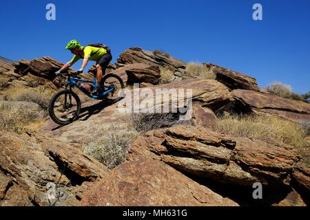 Palm Springs, California, USA. 28th Apr, 2018. Mountain biker rides over steep slickrocks. This is a true Southern California Epic mountain bike ride in the Santa Rosa and San Jacinto Mountains National Monument. Offering huge vistas, off-camber narrow single track, ridges, stream beds, rocks, sand, cactus. This point-to-point route passes a varied array of high desert trails from the foot of the north slope of Santa Rosa Mountains and Agua Caliente Indian Reservation at 4500 feet down to Palm Springs 29 miles away at 500 feet. Credit: Ruaridh Stewart/ZUMA Wire/Alamy Live News - Stock Photo