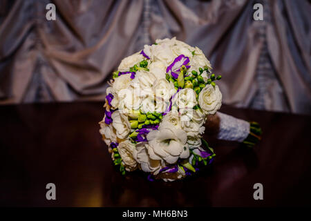 Beautiful bouquet with freesia flowers, wedding flowers bouquet and Eustoma,isolated on wooden table.Lisianthus flowers,violet and white.Flower bouquet. bridal bouquet. Copy space - Stock Photo