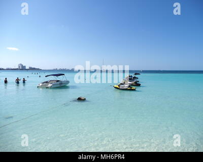 Beauty view of sandy beach panorama at bay of Caribbean Sea in Cancun city in Mexico with jet skis and people in water - Stock Photo