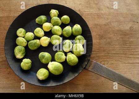 composition of fresh brussels sprouts in an iron pan on a wooden board - Stock Photo