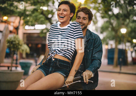 Happy couple going for a bike ride. Woman sitting on boyfriends bicycle handlebar and laughing. - Stock Photo