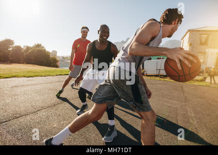 Men playing basketball game on a sunny day. Men practicing basketball skills in play area. - Stock Photo