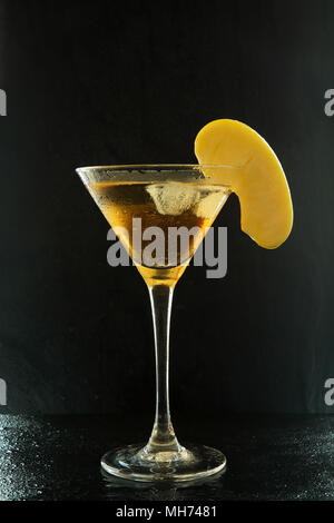 Fresh summer appletini cocktail in a martini glass with an apple slice on a black textured surface with water drops and reflections - Stock Photo