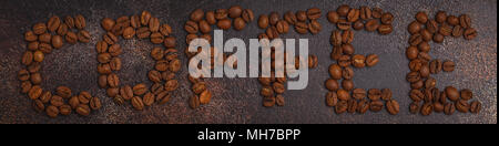 Word coffee made from coffee beans, dark rusty background, top view - Stock Photo