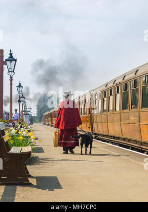 Odd lady, rear view, in costume (Mary Poppins) walking on platform at vintage railway station dog on lead, holding bag, looking at carriages to board. - Stock Photo