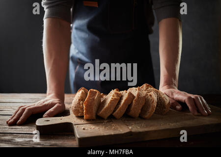 Baker man holding rustic organic loaf of bread in hands rural bakery. - Stock Photo