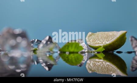 Slice of lime wedge, ice and mint isolated on blue background - Stock Photo