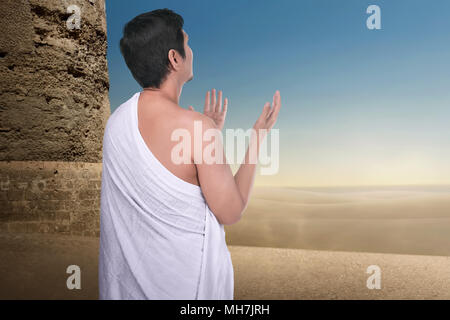 Back view of asian pilgrim man praying to Allah in outdoor - Stock Photo