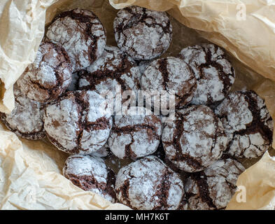 Chocolate crinkle cookies with powdered sugar icing. Cracked chocolate biscuits on paper background.  close up. top view - Stock Photo