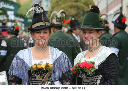 Two participants dressed in traditional costumes  smile for the camera before the start of the Oktoberfest parade in Munich - Stock Photo