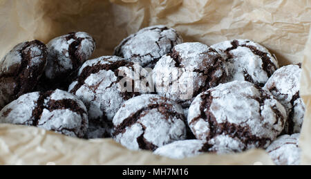 Chocolate crinkle cookies with powdered sugar icing. Cracked chocolate biscuits on paper background.  close up. side view - Stock Photo