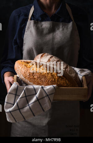 Baker holding fresh homemade bread. Composition in dark colors - Stock Photo