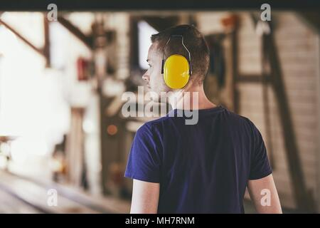 Man working in sawmill. Rear view of the worker with headset. - Stock Photo
