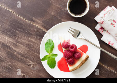 Slice of cheesecake with raspberry sauce and cup of espresso coffee on wooden table. Top view with copy space for text - Stock Photo