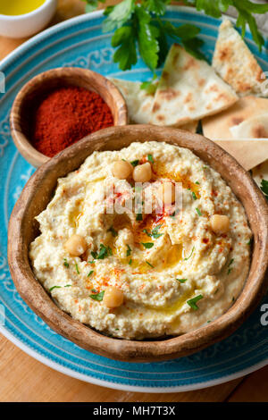 Chickpea hummus with paprika and pita chips. Homemade hummus. Healthy vegan chickpea spread in bowl. Closeup view, selective focus - Stock Photo