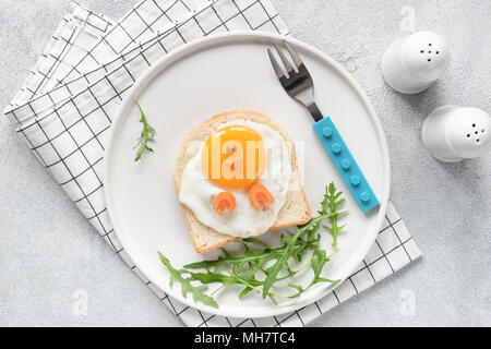 Cute funny breakfast for kids. Chicken shaped sandwich or toast on white plate. Food Art idea. Flat Lay. Table top view - Stock Photo