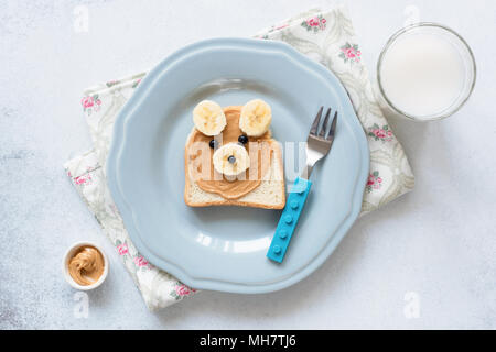 Banana peanut butter toast on a blue plate, meal for kids. Cute funny bear shaped animal toast with nut butter and banana. School lunch for kids. Heal - Stock Photo