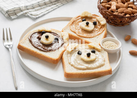 Kids breakfast meal Bread with nut butter and banana. Animal face toast for kids. Healthy breakfast, school lunch for kids. Peanut butter and banana,  - Stock Photo