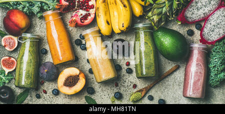 Colorful smoothies in bottles with fresh fruit, copy space - Stock Photo