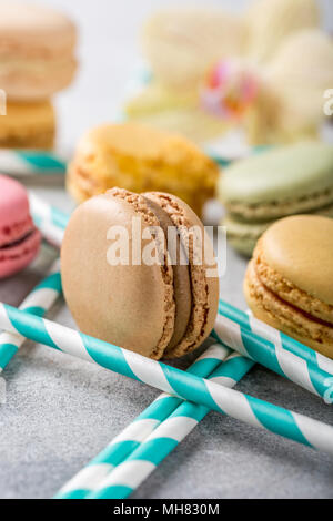 French assorted macarons on light gray concrete background. Holidays food concept. - Stock Photo