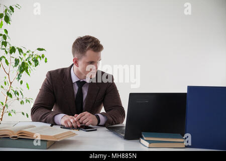a man in a business suit works at the computer with books in the Office - Stock Photo