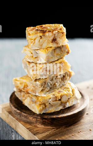 some pieces of typical tortilla de patatas, spanish omelet, on a rustic wooden table, against a black background - Stock Photo