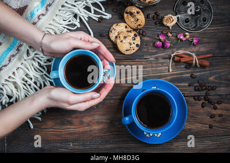 Hands take cup of coffee, coffee beans and cookies-hearts. - Stock Photo