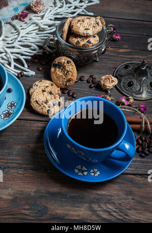 The cup of coffee, coffee beans and cookies-hearts related together on  wooden table. - Stock Photo