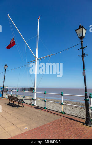A Red Ensign flies on a flagpole on the seafront at Penarth, traditional lamposts on either side and a bench on the Esplanade, Vale of Glamorgan, Wales, UK - Stock Photo