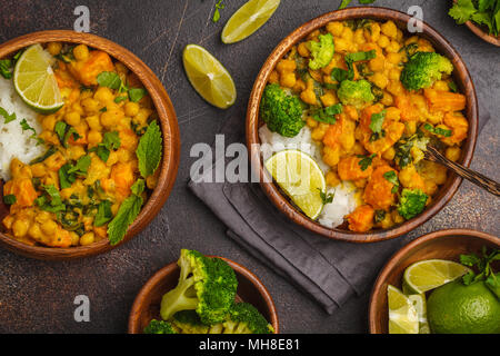 Vegan Sweet Potato Chickpea curry in wooden bowl on a dark background, food flat lay. Healthy vegetarian food concept. - Stock Photo