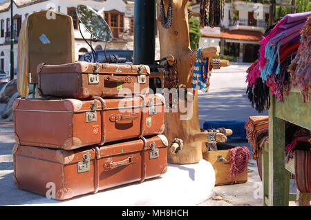 Old things selling at street flea market in Limenas, Thassos, Greece. Three old suitcases stacked on the waterfront are waiting for the buyers. - Stock Photo
