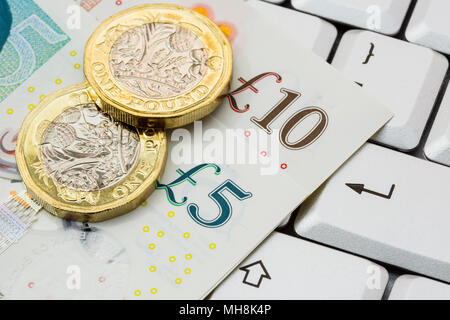 Sterling five and ten pound notes and 2 new pound coins pounds GBP money on a keyboard with enter key. Online investing / shopping concept. England UK - Stock Photo