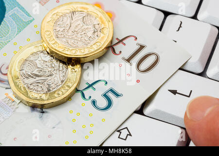 Sterling 5 and 10 pound notes with new pound coins pounds on a keyboard with a person's finger pressing enter key to buy online shopping concept. UK - Stock Photo