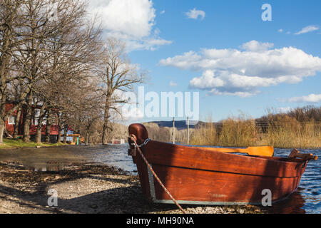 Wooden boat near wooden cottage on the river in the forest - Stock Photo