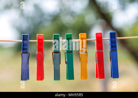 Colorful clothespins on a rope on a blurred background of green foliage - Stock Photo