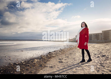 Woman at the beach, showing emotion and expression dealing with anxiety, grief, depression and mental health. - Stock Photo