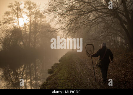 Fisherman walking along canal towpath on a misty cold winter day - Stock Photo