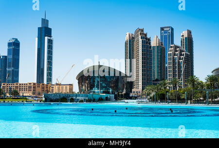 Dubai, United Arab Emirates - March 26, 2018: Dubai Opera and modern Dubai downtown skyscrapers view from Dubai mall at day time - Stock Photo