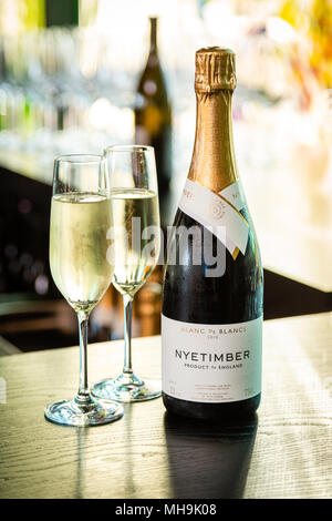 Nyetimber champagne bottle and two filled champagne flutes on a table, blurred background. - Stock Photo