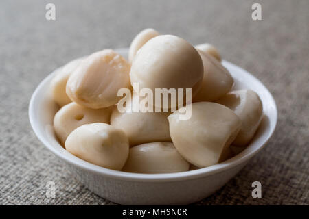 Pickled Garlic Pickles in bowl. Organic Food. - Stock Photo